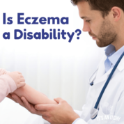 doctor looking at arm - eczema disability